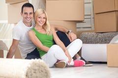 坐在新的家的可爱的夫妇 免版税图库摄影