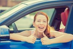 坐在新的汽车里面的妇女司机愉快的微笑的显示的赞许 库存照片