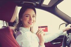 坐在新的汽车里面的愉快的妇女显示信用卡 免版税图库摄影