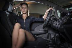 坐在新的汽车里面的美丽的妇女 库存照片