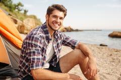 坐在旅游帐篷的微笑的人游人在海滩 免版税库存照片