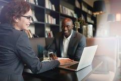坐在旅馆大厅的商人使用手机和膝上型计算机 免版税库存图片