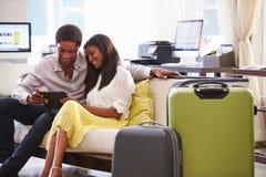 坐在旅馆大厅的夫妇看数字式片剂 免版税库存图片