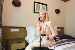 坐在旅馆客房的愉快的女商人 免版税库存照片