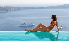 坐在无限水池的边缘和观看风景的可爱的妇女 免版税库存图片