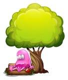 坐在日志上的一个被毒害的妖怪在树下 免版税图库摄影