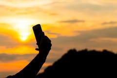 坐在日落期间的少妇剪影和采取与智能手机的一selfie 获得的行家在海滩的乐趣 免版税库存照片