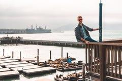 坐在旧金山的年轻人有一个惊人的街市看法在码头39附近 库存图片