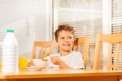 坐在早餐的愉快的男孩吃玉米片 图库摄影