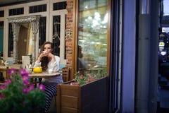 坐在明亮和温暖的咖啡馆的晚上与一杯茶和看窗口的年轻可爱的女孩 街道 库存图片