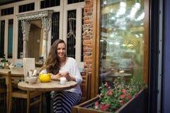 坐在明亮和温暖的咖啡馆的晚上与一杯茶和看窗口的年轻可爱的女孩 街道 图库摄影