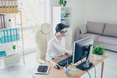 坐在明亮的现代工作站和键入在膝上型计算机的美丽的被聚焦的亚裔年轻女实业家画象  有吸引力的cha 库存照片