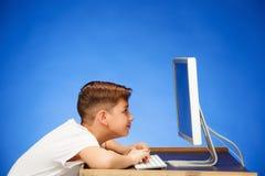 坐在显示器膝上型计算机前面的学龄男孩在演播室 库存照片
