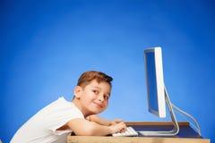 坐在显示器膝上型计算机前面的学龄男孩在演播室 免版税库存照片