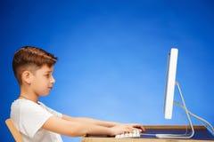 坐在显示器膝上型计算机前面的学龄男孩在演播室 库存图片