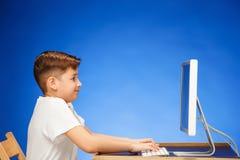 坐在显示器膝上型计算机前面的学龄男孩在演播室 免版税图库摄影
