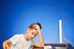 坐在显示器膝上型计算机前面的学龄男孩在演播室 图库摄影