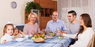 坐在晚餐的桌上的家庭 免版税库存图片