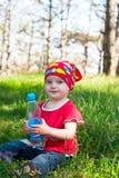 坐在有一个瓶的森林的小甜女孩水 库存图片