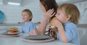 坐在有他的吃汉堡和微笑的母亲和兄弟的厨房里的男婴 健康食品,家庭汉堡 股票视频