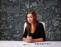 坐在有企业模式和图标的服务台的女实业家 库存照片