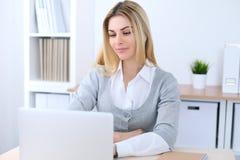 坐在有便携式计算机的办公室工作场所的年轻女商人或学生女孩 家庭企业概念 免版税库存图片