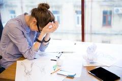 坐在有剪影的办公室的丧失信心的妇女时装设计师 免版税库存照片