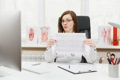 坐在有医疗文件的书桌,心电图纪录,心脏ekg波浪心电图图的年轻女性医生  免版税库存照片
