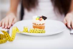 坐在有可口cre的板材前面的年轻节食的妇女 图库摄影