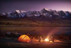 坐在有启发性帐篷的两个人游人在营火附近 图库摄影