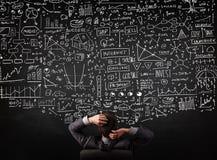 坐在有图的一个黑板前面的商人 免版税库存图片