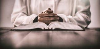 坐在有圣经的书桌的妇女 免版税库存照片