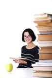 坐在有堆的一张书桌的愉快的妇女书 库存图片