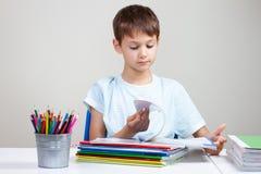 坐在有堆的书桌教科书和笔记本和在家做家庭作业的男孩 免版税图库摄影