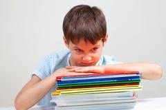 坐在有堆的书桌的恼怒的男小学生教科书和笔记本 免版税库存照片