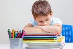 坐在有堆的书桌的生气男小学生教科书和笔记本 图库摄影