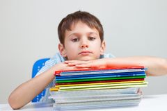 坐在有堆的书桌的生气男小学生教科书和笔记本 库存图片