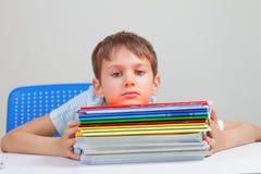 坐在有堆的书桌的生气男小学生教科书和笔记本 免版税库存图片