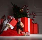 坐在有大圣诞节的红色圣诞老人帽子的亚裔小儿童孩子女孩 库存照片