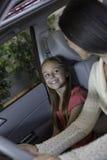 坐在有她的母亲的汽车的女儿 免版税库存照片