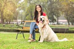坐在有她的狗的一个公园的女孩 免版税库存照片