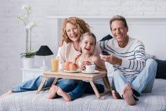 坐在有她的祖父母的早餐盘子的愉快的女孩 免版税图库摄影