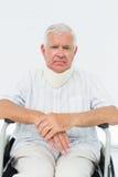 坐在有子宫颈衣领的轮椅的老人 免版税库存图片