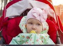 坐在有安慰者的,日落,特写镜头婴儿推车的小女孩,室外, 免版税库存照片