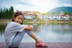 坐在有居住区的自然池塘附近的可爱的女孩 免版税库存照片