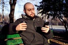 坐在有巧妙的电话和喝的城市公园的年轻人 免版税库存照片
