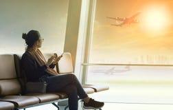 坐在有巧妙的电话的机场终端的旅行的妇女 免版税库存图片
