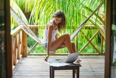 坐在有文件的一个在a的吊床和膝上型计算机的少妇 免版税库存图片