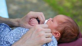 坐在有新生儿的公园的白种人父亲 父母拿着她的胳膊的一个震动的儿童女儿儿子 ?? 影视素材