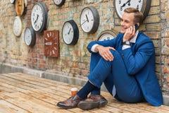 坐在有时钟的墙壁附近的衣服的人 免版税库存图片